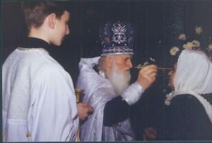 Отец Василий Швец помазывает елеем матушку Маргариту 1994
