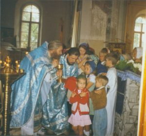 ОТЕЦ ВАЛЕРИЙ ПРИЧАЩАЕТ ДЕТЕЙ В ХРАМЕ. 1994 г.